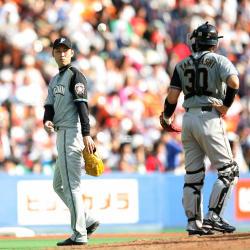 <ロッテ・日本ハム>5回2死一、二塁ベニーに左前安打を打たれ降板する金村(左)は悔しげにボールを捕手・高橋に投げ渡す