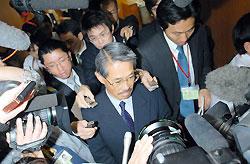退職辞令を受け取り、辞職理由を述べないまま知事室を後にする丸山勝司氏(中央)