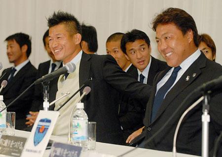 羽田空港で会見に臨む三浦知良(左)と奥寺康彦社長
