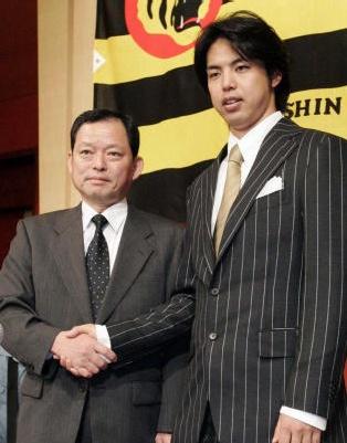 記者会見を終え、阪神の牧田球団社長と握手をする井川