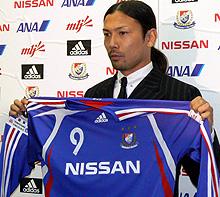 横浜Mのユニフォームを見せる鈴木隆行