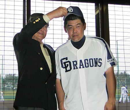 西川球団社長(左)に帽子をかぶせてもらう中村紀洋内野手