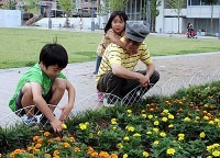 長谷部正さんと一緒に、花壇に植えられた花を眺める孫たち。花の名前など、祖父から教わることもたくさんある(横浜市内で)