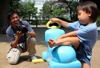 子どもの視線に合わせて、かがんで写真を撮る伊藤さん。子どもを追いかけていると思わず笑みがこぼれる(東京都豊島区で)=松田賢一撮影