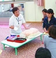 福井県坂井市の子育て支援センターで開かれた「子どものための救急法」講座で指導する子育てマイスターの平井みつ子さん(左)