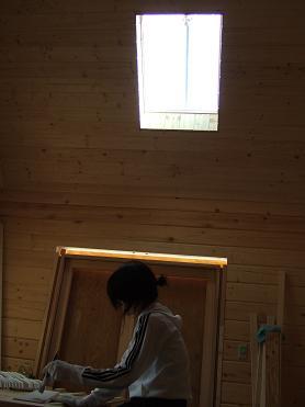 天窓の下で塗装する妻