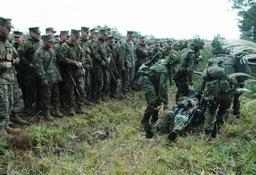 負傷者搬送法を実演する自衛隊員(右)の動きに見入る米海兵隊員