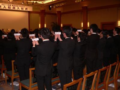 写真キャプション=式の最後に「マルハンイズム」を大きな声で唱和する新入社員